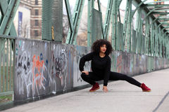 African girl with curly hair. Beautiful African woman doing acrobatics on a bridge royalty free stock photo