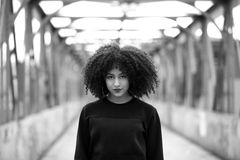 African girl with curly hair. Beautiful African woman standing on a bridge Stock Images