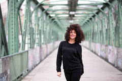 African girl with curly hair. Beautiful African woman standing on a bridge stock photography