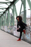 African girl with curly hair. Beautiful African woman standing on a bridge royalty free stock images