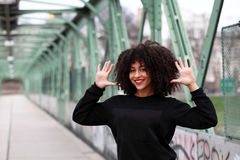 African girl with curly hair. Beautiful African woman standing on a bridge stock image