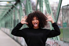 African girl with curly hair. Beautiful African woman standing on a bridge royalty free stock image