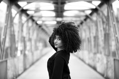 African girl with curly hair looking over her shoulder. Beautiful African woman standing on a bridge Royalty Free Stock Photo