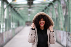 African girl with curly hair smiling. Beautiful African woman standing on a bridge Royalty Free Stock Photos