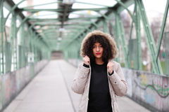 African girl with curly hair in winter jacket. Beautiful African woman standing on a bridge Royalty Free Stock Images