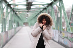 African girl with curly hair in winter jacket. Beautiful African woman standing on a bridge Stock Photography