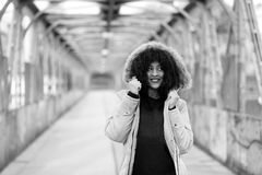 African girl with curly hair in winter jacket. Beautiful African woman standing on a bridge Stock Images