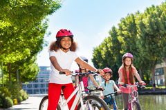 African girl cycling with friends at city park Royalty Free Stock Images