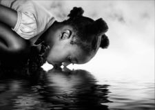 African girl drinking from a river.