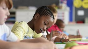 African girl at elementary school. Smiling african girl sitting at desk in class room and looking at camera. Portrait of young black schoolgirl studying with stock video