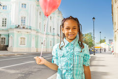 African girl with flying balloon stands on street Stock Photos