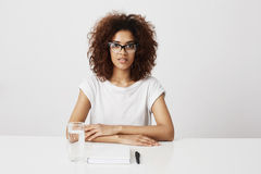 African girl in glasses looking at camera sitting over white background. Copy space. Stock Photography