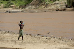 African girl goes on the river bank Stock Images