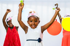 African girl holding balloons with friends in background. Royalty Free Stock Photos