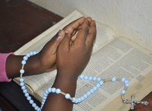 African girl holding a rosary on an open bilble Royalty Free Stock Photo