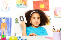 African girl holds flashcard with zero at  desk. African girl holds flashcard with zero number at the desk while sitting in playroom with wall behind which is Royalty Free Stock Image