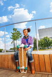 African girl holds skateboard and sitting on side Royalty Free Stock Photo