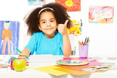 African girl holds thumbs up at the desk writing royalty free stock photos