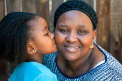 African girl kissing mother on cheek. Royalty Free Stock Images
