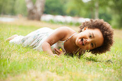 African girl is laying down. African young girl is having fun outside stock images