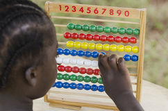 African girl learning to count. Little african girl counting on abacus frame on blurred background Royalty Free Stock Photography