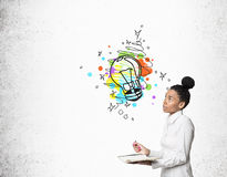 African girl with notebook and colorful light bulb Stock Photos