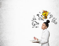 African girl with notebook with question marks and light bulb Royalty Free Stock Image