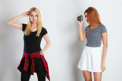African girl photographing blonde woman Stock Photography