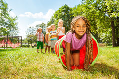 African girl play crawling through tube in park. Kids play with tube on the lawn with little blond beautiful black girl with African brides crawling out and her Royalty Free Stock Photo