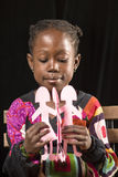 African girl playing with paper dolls Royalty Free Stock Image