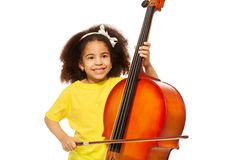 African girl plays violoncello with fiddlestick. Happy African girl holds fiddlestick and plays violoncello standing on the white background stock photos