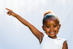 African girl pointing at corner with finger. Royalty Free Stock Images