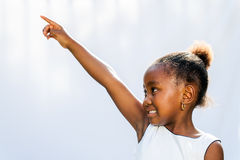 African girl pointing and looking at corner. Stock Photography