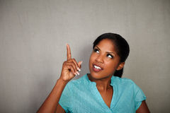 African girl pointing up while looking away Royalty Free Stock Images