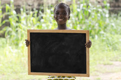 African girl posing outdoors with a blackboard. Girl standing and holding signboard and looking at camera in front of building Stock Photos