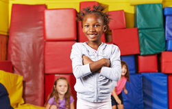 African girl in preschool gym. African girl with her arms crossed smiling in a preschool gym Royalty Free Stock Images