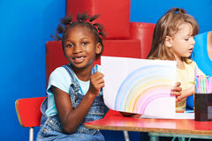 African girl with rainbow drawing. On piece of paper in kindergarten royalty free stock photography