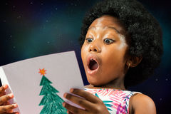 African girl reading christmas card. Stock Photography