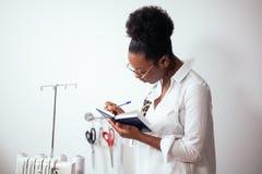 African girl seamstress making notes at notebook. designer drawing sketches. African girl seamstress making notes at notebook. Fashion designer drawing sketches Royalty Free Stock Photography