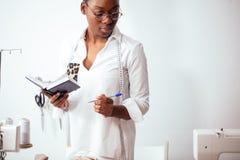 African girl seamstress making notes at notebook. designer drawing sketches. African girl seamstress making notes at notebook. Fashion designer drawing sketches Royalty Free Stock Photos