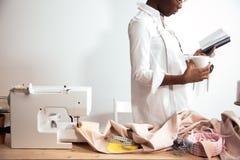 African girl seamstress making notes at notebook. designer drawing sketches. African girl seamstress making notes at notebook. Fashion designer drawing sketches Stock Photos