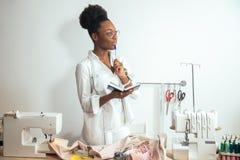 African girl seamstress making notes at notebook. designer drawing sketches. African girl seamstress making notes at notebook. Fashion designer drawing sketches Stock Photography