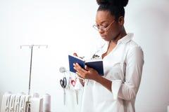 African girl seamstress making notes at notebook. designer drawing sketches. African girl seamstress making notes at notebook. Fashion designer drawing sketches Royalty Free Stock Photo