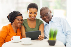 African girl senior parents. Pretty young adult african girl with senior parents using tablet computer Stock Photo