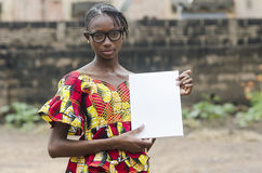 African Girl Showing her Homework. Young african girl in eyeglasses holding papers outdoors with blurred background Royalty Free Stock Photo