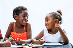 African girl showing thumbs up to friend at desk. Stock Images