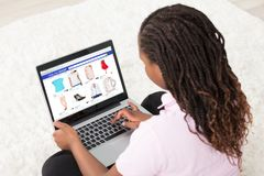 African Girl Doing Online Shopping. African Girl Sitting On White Carpet Doing Online Shopping Using Laptop At Home stock image