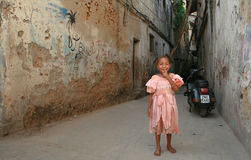 African girl smiling, standing in a courtyard dilapidated stone Stock Photography