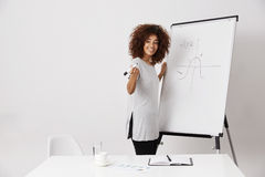 African girl smiling standing near marker whiteboard over white background. Beautiful african girl smiling standing near marker whiteboard over white background Stock Photos