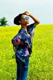 African girl stands with his hands on the field with yellow flowers and looks at the sun. African American girl wearing sunglasses, jeans and a tunic, stands Stock Photos